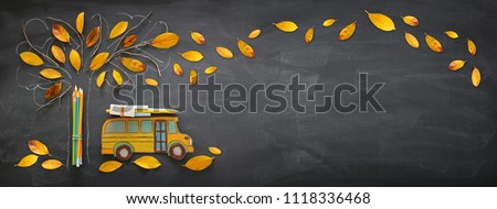 Back to school concept. Top view banner of school bus and pencils next to tree sketch with autumn dry leaves over classroom blackboard background - Shutterstock ID 1118336468