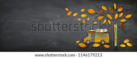 Back to school concept. Top view banner of school bus and pencils next to tree sketch with autumn dry leaves over classroom blackboard background #1146179213