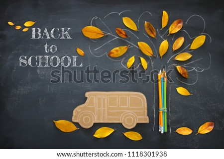 Back to school concept. Top view image of school bus and pencils next to tree sketch with autumn dry leaves over classroom blackboard background #1118301938