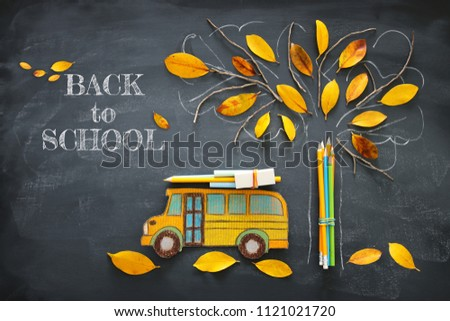 Back to school concept. Top view image of school bus and pencils next to tree sketch with autumn dry leaves over classroom blackboard background #1121021720