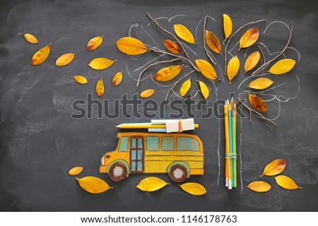 Back to school concept. Top view image of school bus and pencils next to tree sketch with autumn dry leaves over classroom blackboard background #1146178763
