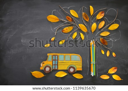 Back to school concept. Top view image school bus and pencils next to tree sketch with autumn dry leaves over classroom blackboard background #1139635670