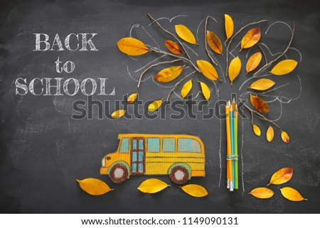 Back to school concept. Top view image school bus and pencils next to tree sketch with autumn dry leaves over classroom blackboard background #1149090131