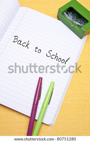 Back to School Concept with Message on Open Notebook with Pens and Paperclips on Yellow Background.