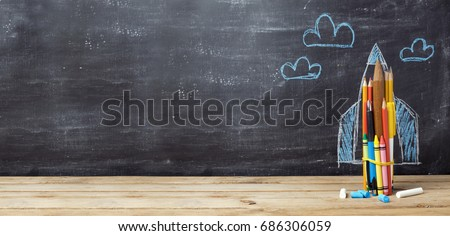 Back to school concept with rocket made from pencils over chalkboard background #686306059