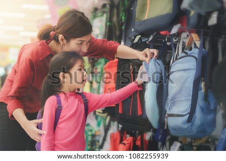 Back to school concept, Young asian mother or parent and little girl kid  buying school satchel or bag in store, Selective focus