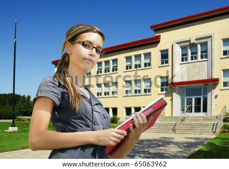 Back to school: confident young female student with books in front of school entrance. Could be college or small university campus.