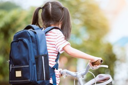 Back to school. Cute asian child girl with backpack biking a bicycle and going to school with fun