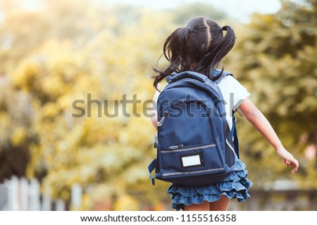 Back to school. Cute asian child girl with backpack running and going to school with fun #1155516358