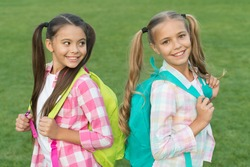 Back to school. Cute schoolgirls with long ponytails. Ending of school year. Cheerful smart schoolgirls. Happy schoolgirls outdoors. Small schoolgirls with backpacks. September. Vacation is over.