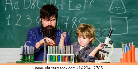 Back to school. Early development of children. Experiments in chemistry laboratory. father and son at school. teacher man with little boy. School education. science experiment in classroom activities.