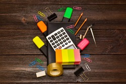 Back to school. Education concept. Office supplies, pens, pencils, wash, notebook, paper clips, pair of compasses, paper on wooden background.