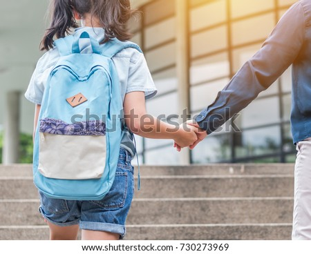 Back to school first day education concept with girl kid (elementary student) carrying backpacks holding parent woman or mother's hand walking up school building stair going to class