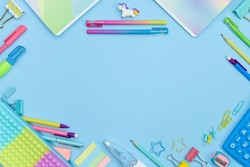 Back to School frame with copy space. Collection of colorful school supplies in a bright flat style. Educational concept. Unicorn, calculator, pencil case, pencils, sharpeners and curly paper clips.