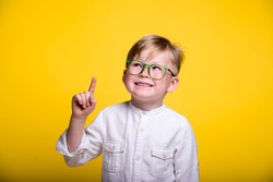 Back to school. Funny child in glasses pointing up on yellow background. Pupil from elementary school  Success, bright and creative ideas, innovation technology concept.