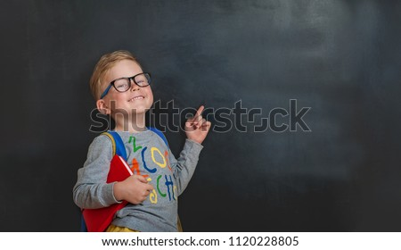 Back to school. Funny little boy in glasses pointing up on blackboard. Child from elementary school with book and bag. Education.
