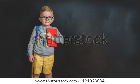 Back to school. Funny little boy in glasses with backpack and book against blackboard. Child from elementary school. Education. #1121023034
