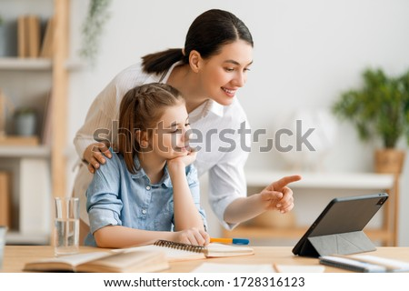 Back to school. Happy child and adult are sitting at desk. Girl doing homework or online education.