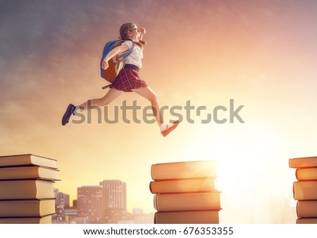 Back to school! Happy cute industrious child running and jumping on books on background of sunset urban landscape. Concept of education and reading. The development of the imagination.