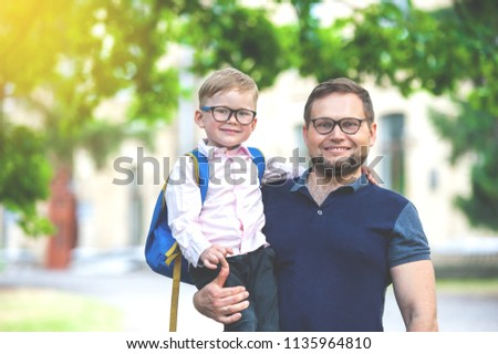 Back to school. Happy father and son go to elementary school. Parent take child to primary school. Pupil go study with backpack. Beginning of lessons. First day of fall.