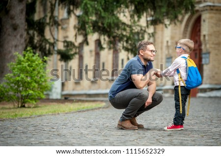 Back to school.  Happy father and son go to elementary school. Parent taking child to primary school. Pupil go study with backpack. Beginning of lessons.  First day of fall.  #1115652329