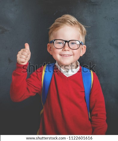 Back to school. Happy little boy in glasses with thumb up and backpack against blackboard.  #1122601616