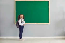 Back to school. Happy schoolgirl is standing smiling on the background of the school blackboard in the classroom. Learning education lecture development of children of students at school lyceum.