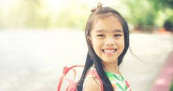 back to school. Happy smiling girl from elementary school at the school yard.