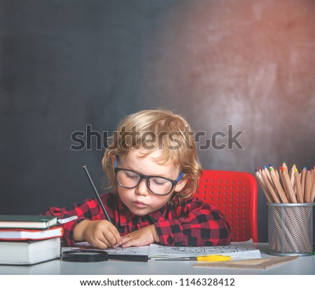 Back to school. Happy smiling pupil drawing at the desk. Child in the class room with blackboard on background. Alarm clock, pencils, books. Kid girl from primary school. first day of fall. - Shutterstock ID 1146328412