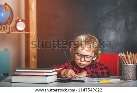 Back to school. Happy smiling pupil drawing at the desk. Child in the class room with blackboard on background. Alarm clock, pencils, books. Kid girl from primary school. first day of fall. - Shutterstock ID 1147549622
