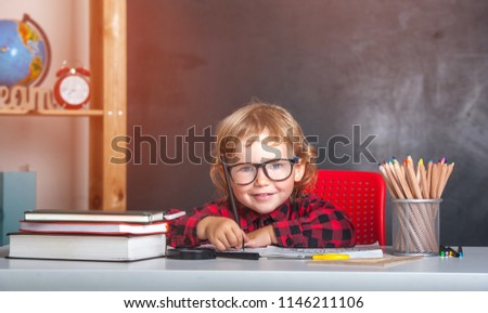 Back to school. Happy smiling pupil sitting at the desk. Child in the class room with blackboard on background. Alarm clock, pencils, books. Kid girl from primary school. first day of fall. - Shutterstock ID 1146211106