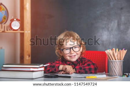 Back to school. Happy smiling pupil sitting at the desk. Child in the class room with blackboard on background. Alarm clock, pencils, books. Kid girl from primary school. first day of fall. - Shutterstock ID 1147549724