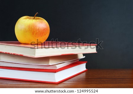 Back to school. Image of blank teacher's desk with a pile of textbooks and apple