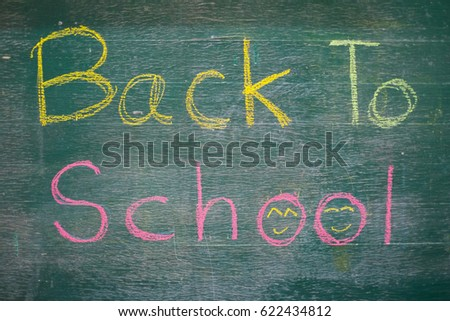 Back to school message on Blackboard inscribed with colorful chalk for background. #622434812