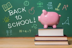 Back to School message with pink piggy bank on top of books with chalkboard