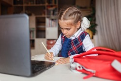 Back to school, new normal education. Cute girl in school uniform writing with pencil during online lesson. Social distance learning and new guidance