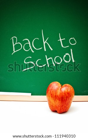 Back to school note written with white chalk on a green chalkboard, a red apple  in front of the board.