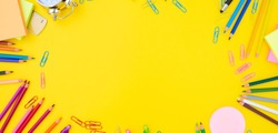 back to school or office styed scene with multicolored school supplies on yellow background banner