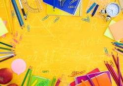 back to school or office styed scene with multicolored school supplies on yellow with math formulas