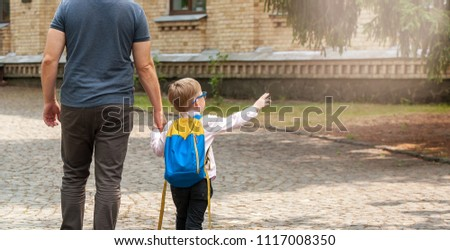 Back to school. Parent taking child to school. Pupil of primary school go study with backpack. Child point. Beginning of lessons. First day of fall.