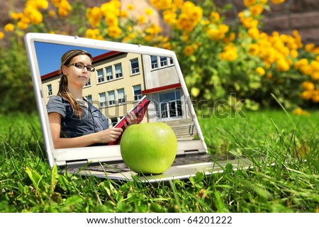 Back to school: Picture on laptop screen of confident young female student holding books and standing in front of school building entrance.
