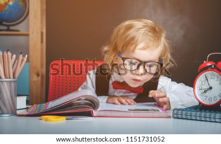 Back to school. Pupil from primary school is reading a book. Child in the class room with blackboard on background. Alarm clock, pencils, books. Kid girl from primary school. first day of fall.