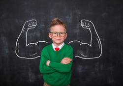 Back to school. Pupil with muscles drawn on blackboard. Portrait of strong winner businessman in office. Success in business concept. Copy space for your text