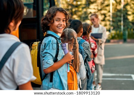 Back to school. Pupils of primary school with teacher near school bus. Happy children ready to study. Stock photo ©