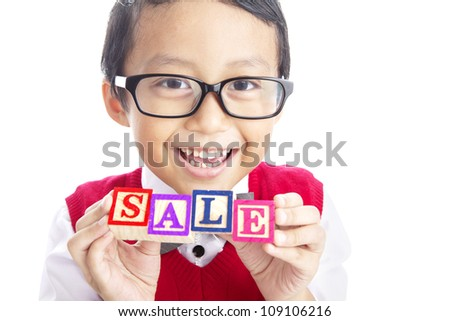 Back to School Sale concept; Portrait of asian elementary school student showing letter blocks spelling out SALE. - stock photo