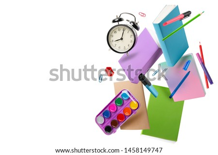 Back to school 1 September. Flying books, notebooks, pencils and alarm clock isolated on white
