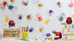 Back to school stationery is on the table. Colorful hand prints background