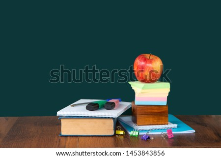 Back to school. Still life with school supplies. Blackboard in chalk chalkboard. Green background. Notebooks, notebooks, felt-tip pens, colored pencils. Beginning of the school year. Copy space.