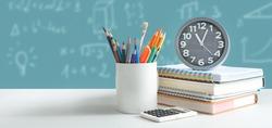 Back to school, student stuff on desk, board in backround