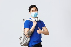 Back to school, studying on covid-19, education and university life concept. Handsome hipster guy, asian freshman student in medical mask, show thumb-up as head classes with backpack and headphones